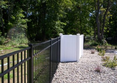 Starling style aluminum pool fence by OnGuard goes well with any of the Illusions Vinyl Fence styles and colors. The vinyl fence here works as both a sound buffer and to hide the unsightly filter.
