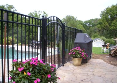 Black fence is timeless. Black fence is also the undisputed favorite color for pool fence. You can see here that it blends well with the pavement and the arched top gate with ball caps on the posts make this one beautiful entry. OnGuard offers sveveral enhancements for the Starling style that can add even more appeal to your pool enclosure. Check out the OnGuard page for more details.