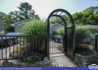 Eastern Ornamental Aluminum Fence Style EO40V two rail, 48 inch tall BOCA pool code compliant fence. The accent gate is set in a Grand Illusions Arbor L-105 Black with small diagonal lattice side panels.