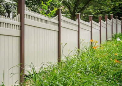 V3706 style - Stepped Victorian picet top by Illusions vinyl fence in Grand Illusions L102 Tan and posts in L106 Brown Grand Illusions colors.