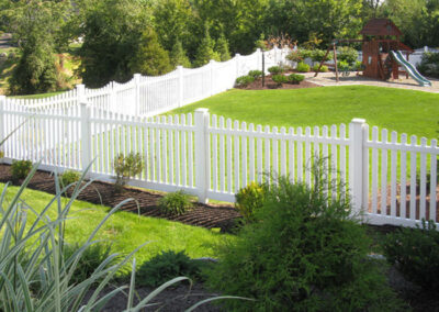 An Illusions Vinyl contemporary space picket fence with a scalloped top