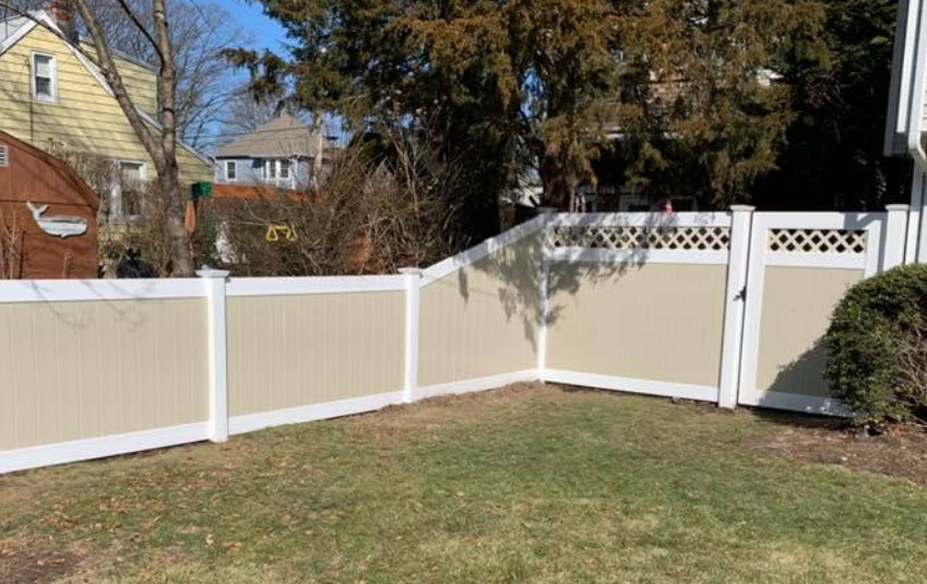Illusions vinyl fence with Classic White rails and Beige boards with a 6 to 4 transition panel on the left an Illusions fence style V3215D-6 with a matching gate.